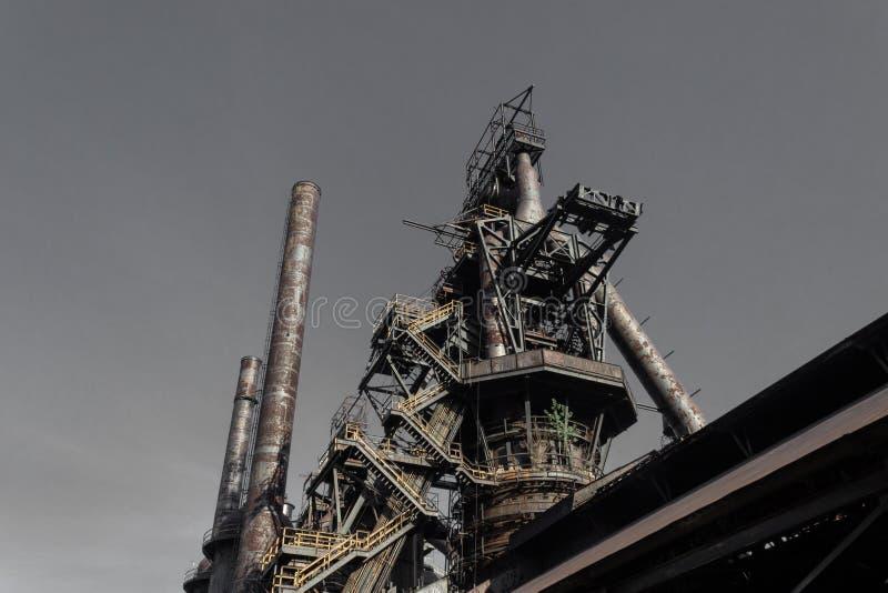 Монументальный взгляд старого сталелитейного завода со спуская лестницей, дымовыми трубами стоковая фотография rf