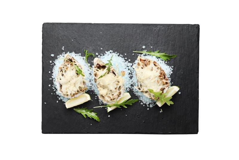 Морепродукты на голубом соли моря с сыр и известка на плите шифера изолированной на белой предпосылке стоковые фотографии rf