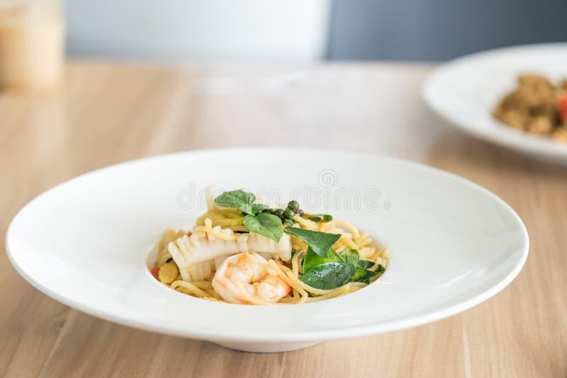 Морепродукты спагетти пряные с базиликом на плите стоковое фото