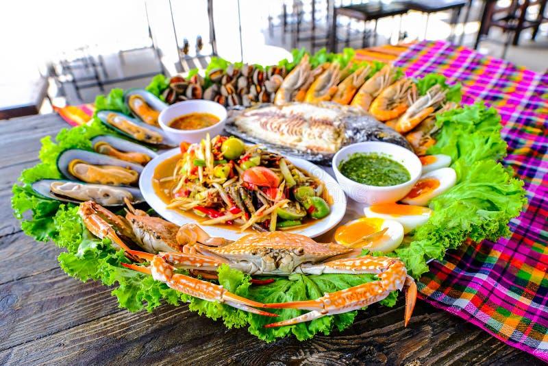 Морепродукты Somtum имеют clams, креветку, крабов, вареные яйца, зажаренную тилапию, помещенную в красиво помещенном подносе на д стоковые фотографии rf