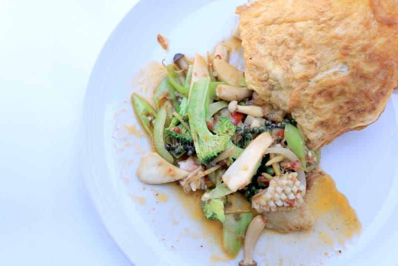 Морепродукты зажаренные Stir пряные с черным перцем и тайским омлетом стиля с рисом на белом блюде, тайской пряной еде травы/изоб стоковое фото rf