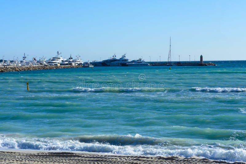 Море бирюзы, белые яхты, маяк и следы ноги в песке на солнечный день Канн, Франция Известное Croisette и стоковая фотография rf