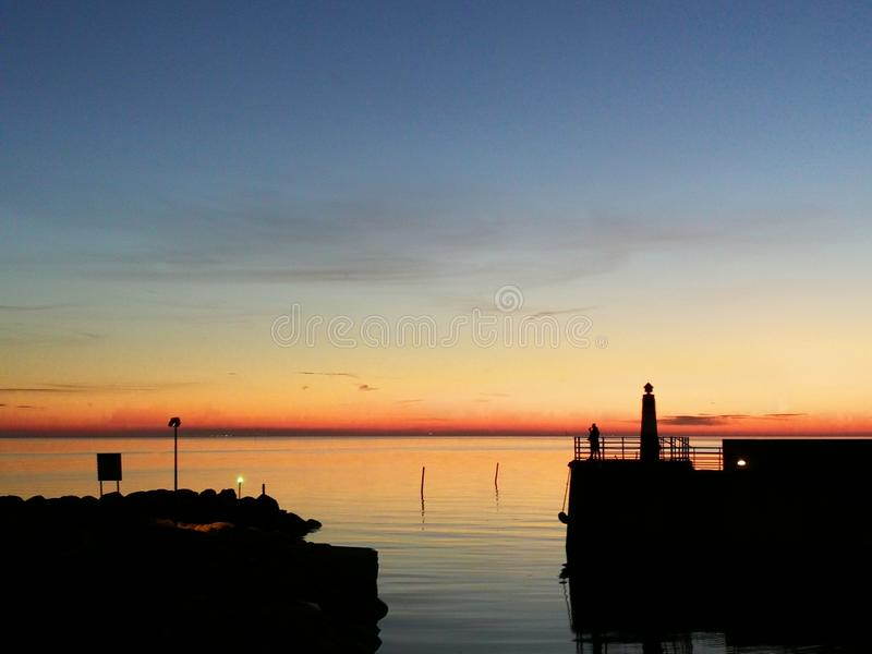 Море и заход солнца на заливе стыковки Марины в Malmo Швеции стоковая фотография rf