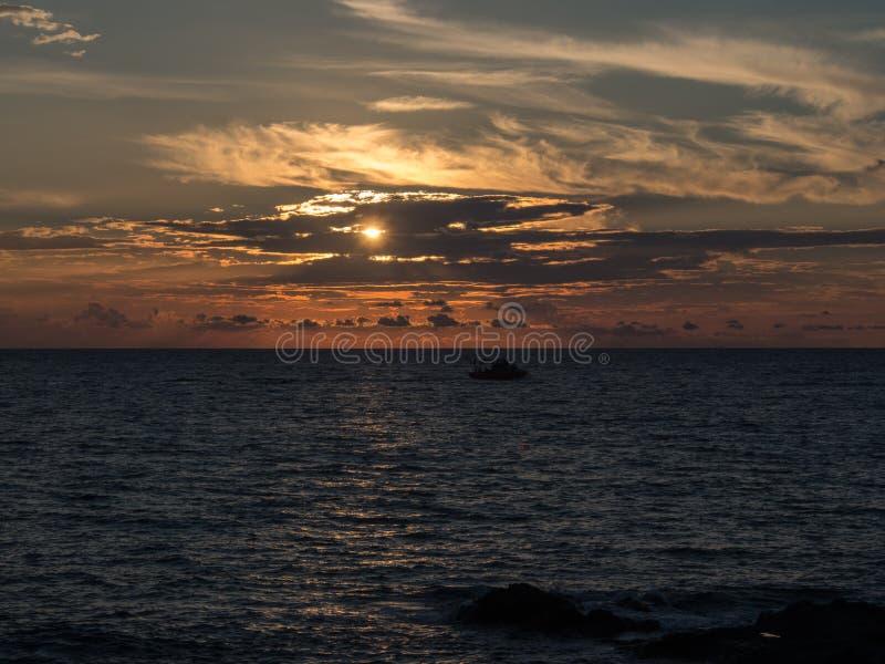 Море и шлюпка на заходе солнца Pantelleria, Сицилия, Италия стоковые фотографии rf