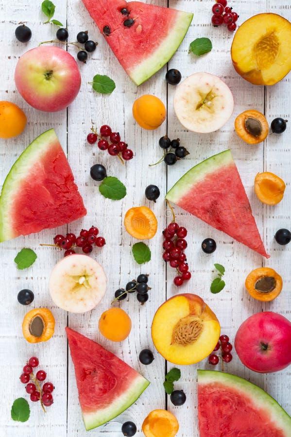 море конца крушины ягоды предпосылки вверх Много плодоовощи и ягод лета разбросаны на белую деревянную предпосылку стоковые фотографии rf