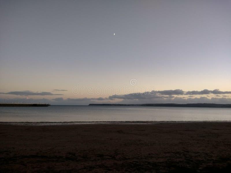 Море при малая луна смотря прищурясь через облако стоковое фото