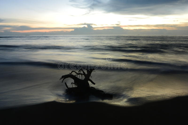 Море пляжа песка перемещения природы захода солнца красивое заволакивает момент дня светлый изумительный стоковое фото rf