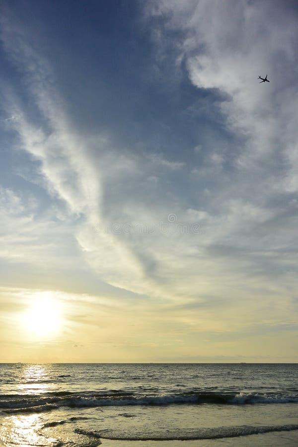 Море пляжа песка перемещения природы захода солнца красивое заволакивает момент лета воды дня изумительный стоковое фото