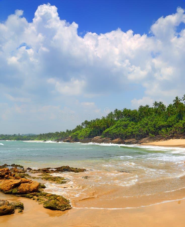 Море развевает на тропическом пляже с камнями и утесами стоковые фото