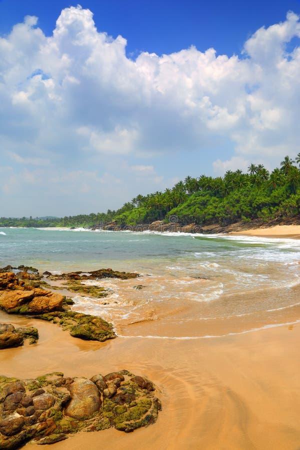 Море развевает на тропическом пляже с камнями и утесами стоковое изображение