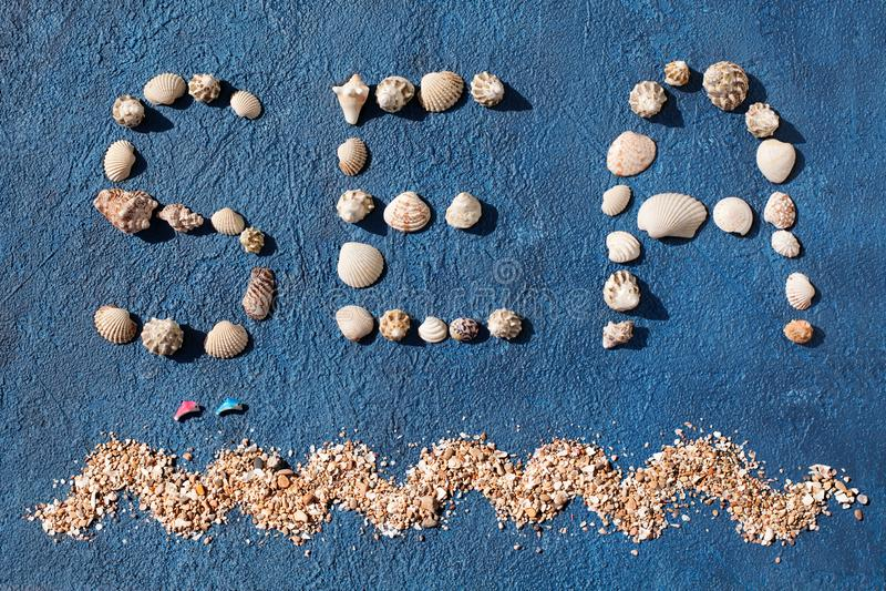 Море сделанное seashells, декоративная волна слова моря, золотой песок, 2 скача дельфина на голубом конце взгляда сверху предпосы стоковое фото rf