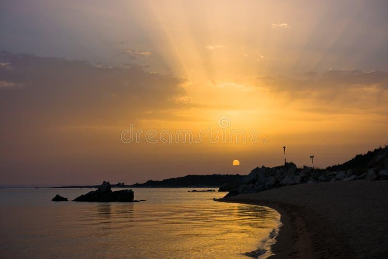 Море трясет на песчаном пляже на заходе солнца, западном побережье полуострова Sithonia, Chalkidiki стоковые фотографии rf