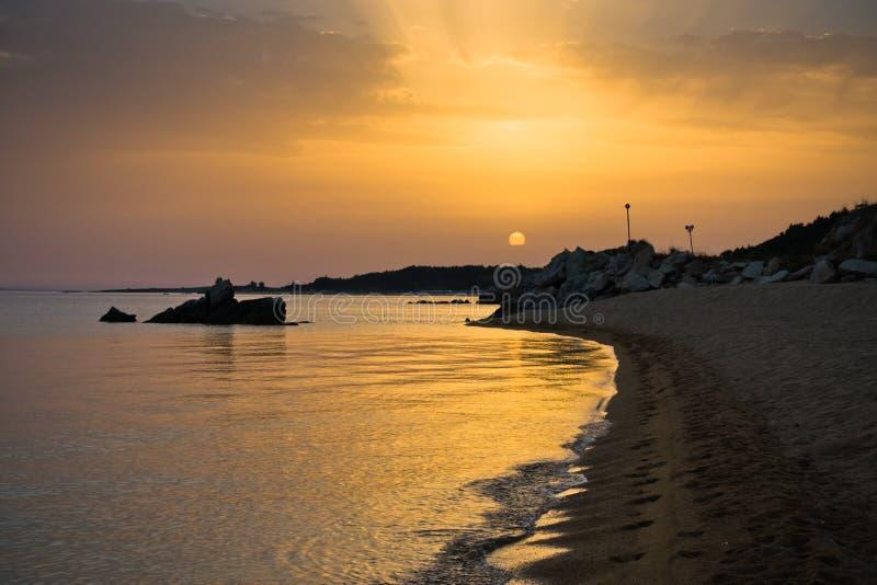 Море трясет на песчаном пляже на заходе солнца, западном побережье полуострова Sithonia, Chalkidiki стоковые фото