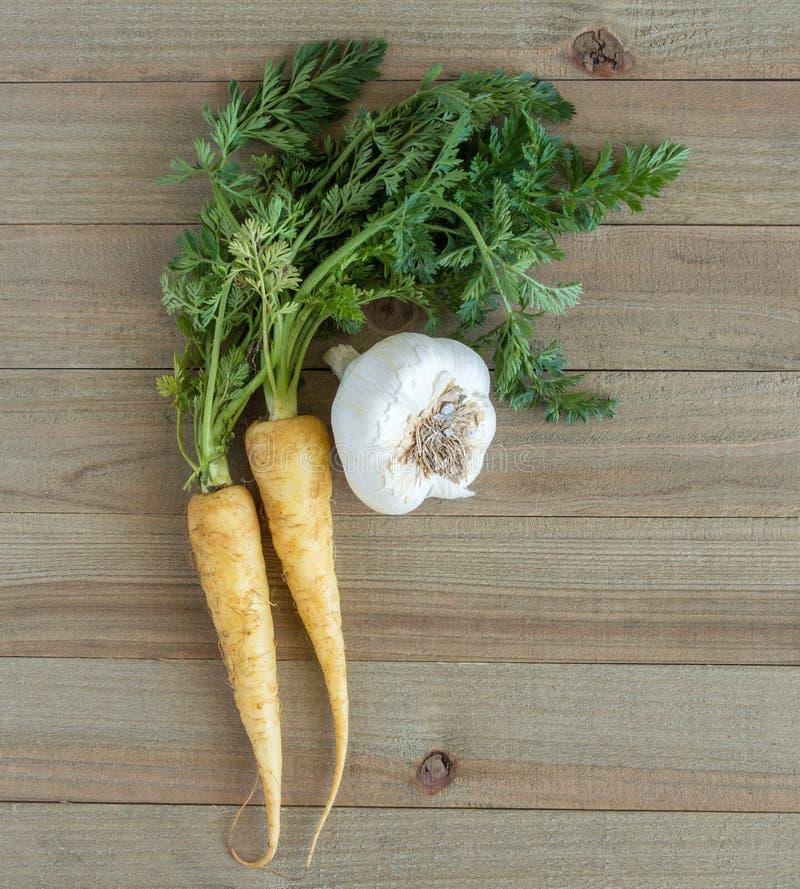 Моркови младенца белые, и шарик чеснока на деревянной предпосылке стоковое фото rf