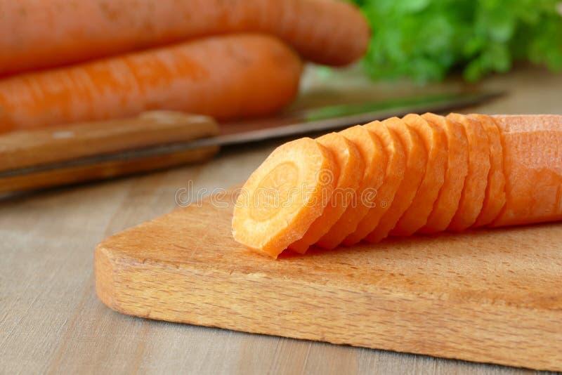 Моркови, отрезанные в кругах, лож на разделочной доске на предпосылке морковей стоковые изображения rf