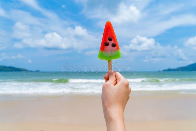 Мороженое арбуза удерживания руки женщины на пляже во время праздников перемещения отдыхает outdoors на океане или море природы в стоковые изображения rf