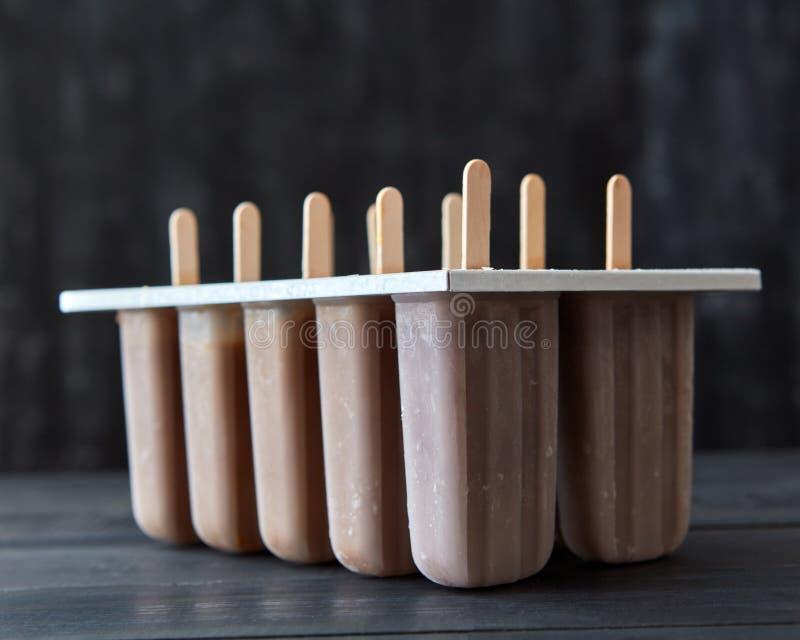 Мороженое кофе на ручке в пластмассе отливает в форму на темной деревянной предпосылке Десерт лета стоковое фото