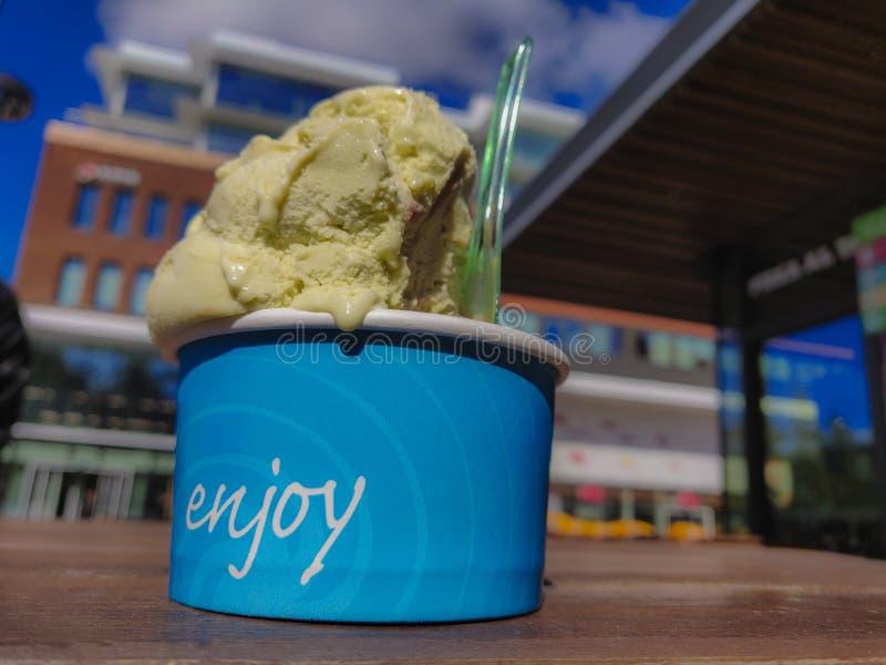 мороженое плавя во для того чтобы насладиться чашкой с ложкой во время европейского лета на таблице стоковое изображение rf