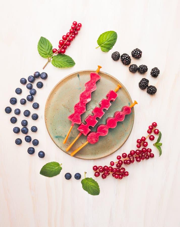 Мороженое ягод хлопает с красной смородиной, ежевиками, голубиками и пипермент выходит, составляющ на белую деревянную предпосылк стоковое изображение rf