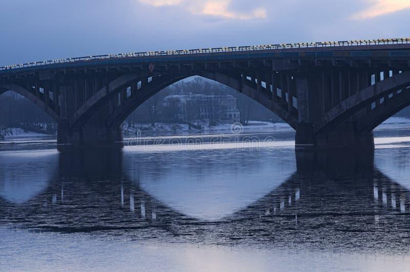 Морозный рано утром Мост метро отраженный в воде С другой стороны вы можете увидеть белое здание Kyiv Украина стоковое изображение