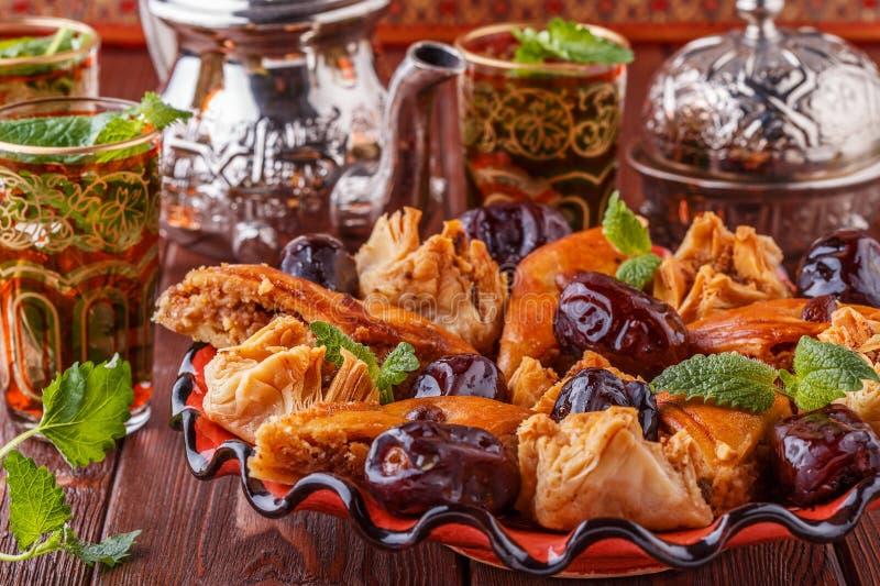 Морокканский чай мяты в традиционных стеклах с помадками стоковая фотография