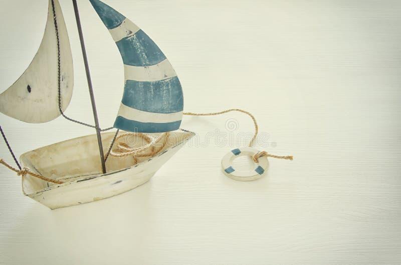 морская концепция с белым декоративным парусником над белым деревянным столом изображение фильтрованное годом сбора винограда стоковые изображения