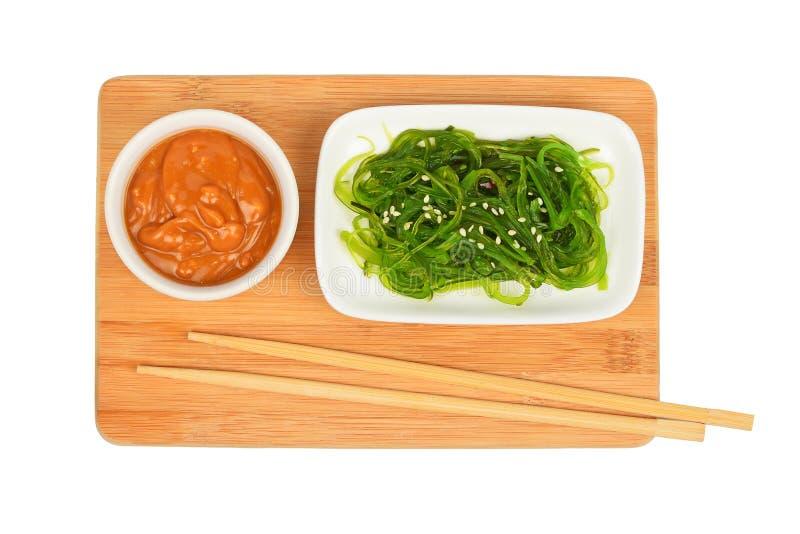 Морские водоросли салат и арахис sauce на бамбуковой доске стоковое фото