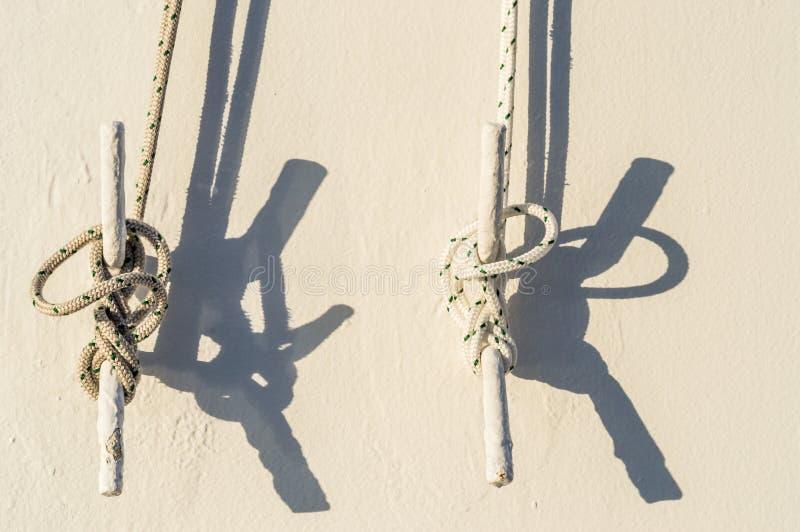 2 морских веревочки связанной к зажимам металла на стене туристического судна стоковые изображения