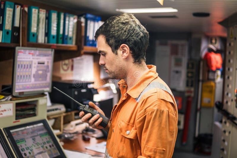 Морской инженер работая на радиосвязи на комнате контроля двигателя стоковое изображение rf