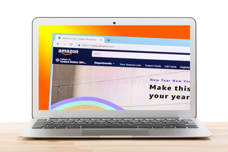 Москва, Россия - июль 2018: Домашняя страница сети Амазонки онлайн ходя по магазинам на дисплее ноутбука против изолированной пре стоковая фотография rf