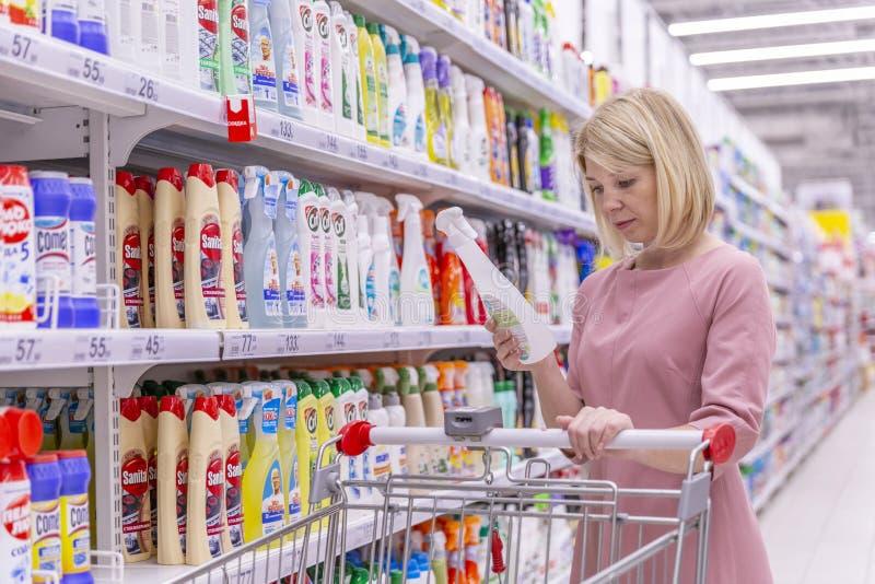Москва, Россия, 07 24 2019: Молодая женщина в отделе химикатов домочадца в супермаркете выбирает продукт стоковое изображение rf