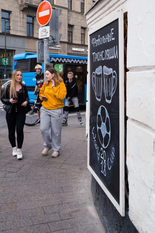 МОСКВА, РОССИЯ - 30-ОЕ АПРЕЛЯ 2018: Люди около доски на proezd Solyansky с рекламой футбола передают стоковая фотография rf