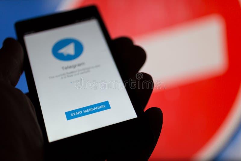МОСКВА, РОССИЯ - 16-ОЕ АПРЕЛЯ 2018: Мобильный телефон с телеграммой app в руке против запрещая знака Телеграмма запрещенная в Рос стоковое изображение rf