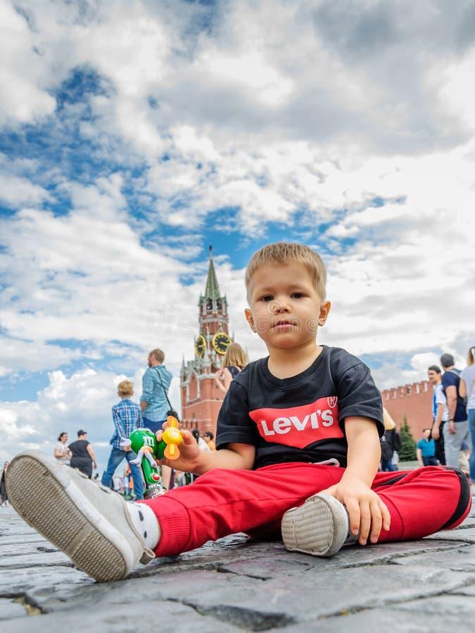 Москва, Россия - 7-ое июля 2018: мальчик сидит на камнях красной площади вымощая, предпосылке от башни Spassky, голубого неба стоковые фотографии rf