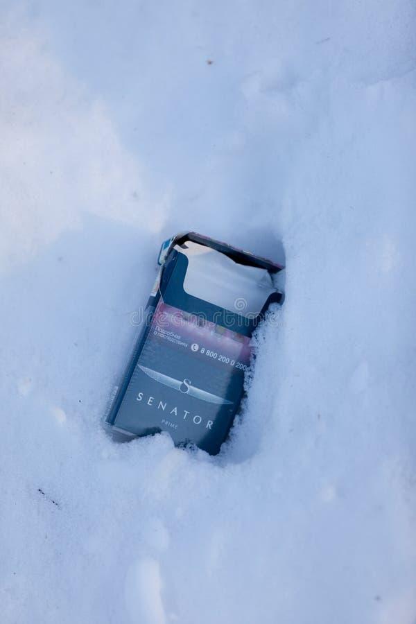 МОСКВА, РОССИЯ - 20-ОЕ МАРТА 2018: Пустой пакет сигареты на покрытом снег переулке парка стоковое фото