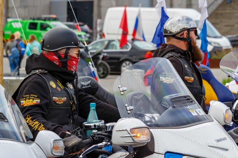 Москва, Россия - 4-ое мая 2019: Велосипедисты в шлемах и оборудовании с атрибутами сидят на туристском крыле золота Honda мотоцик стоковое изображение