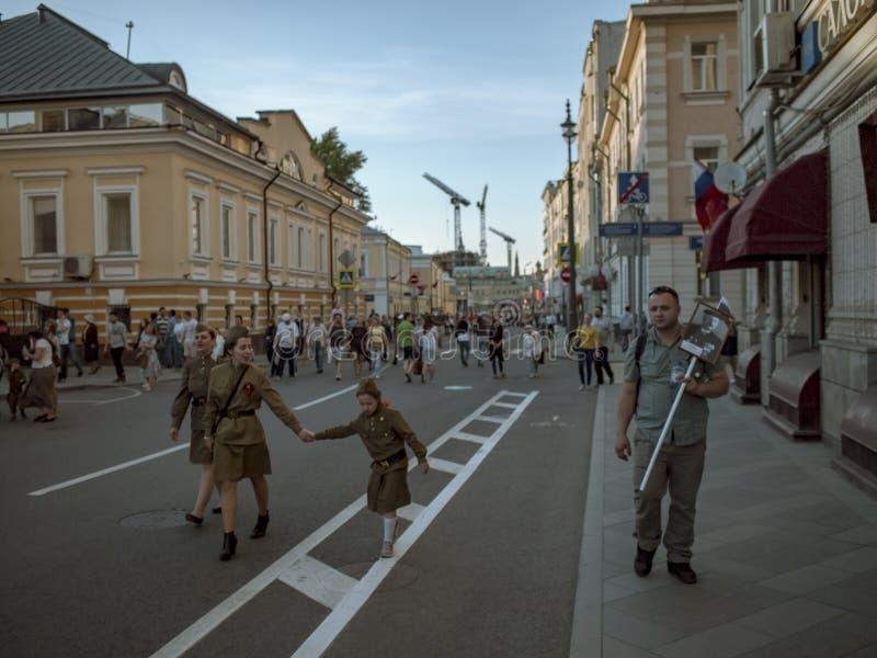 МОСКВА, РОССИЯ - 9-ОЕ МАЯ 2016: 3 девушки в воинской исторической одежде и человеке с портретом ` s предшественника идут вперед стоковая фотография