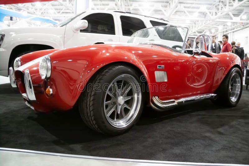 Москва, Россия - 25-ое мая 2019: Красный с автомобилем белых нашивок винтажным ретро Стойки кобры 427 Shelby в выставочном зале стоковые фото