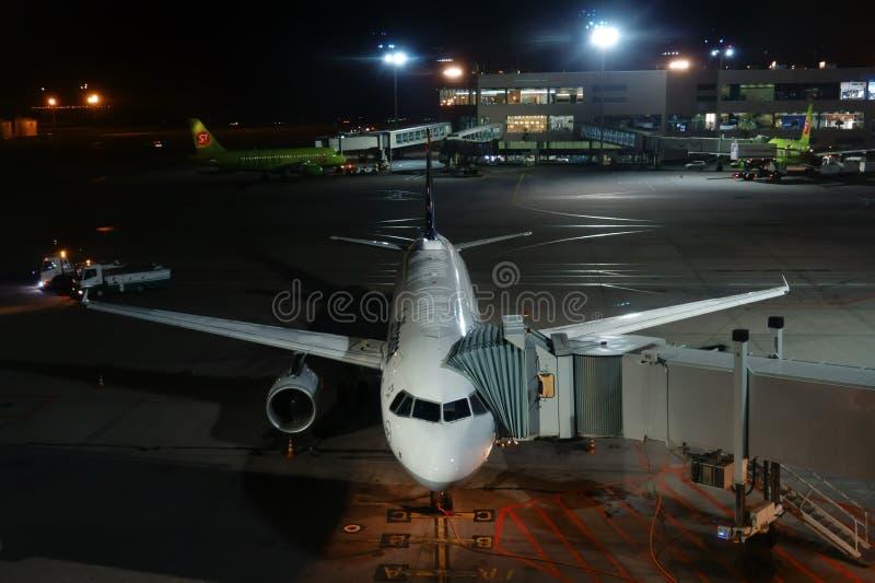 МОСКВА, РОССИЯ - 2-ОЕ СЕНТЯБРЯ 2017: авиапорт Domodedovo на ноче, выбирая вверх самолет перед отклонением Дозаправлять и нагружат стоковое фото rf
