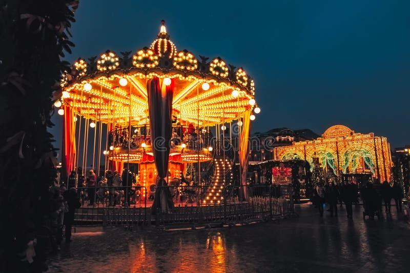 МОСКВА, РОССИЯ ЯНВАРЬ 2017: Люди на carousel около красной площади украшенной и аранжированной на Новый Год рождества Светящая ка стоковое изображение