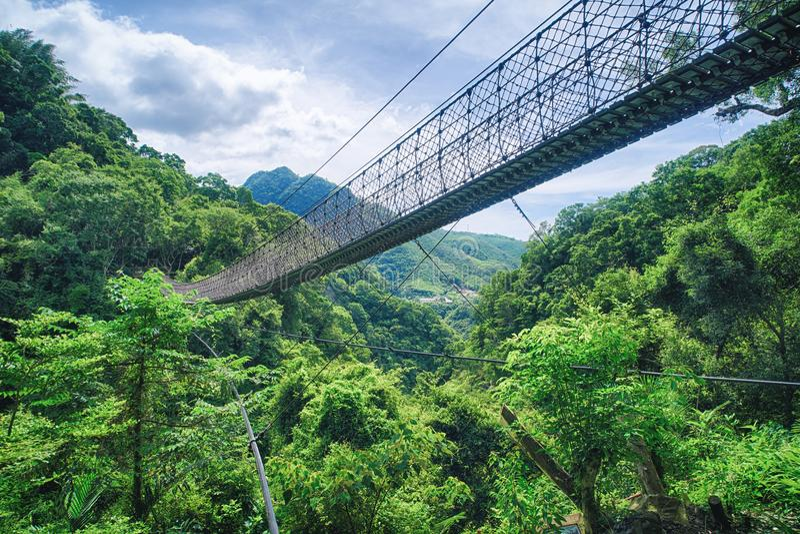 Мост веревочки на солнечный день, съемка неба Xiao Wulai в живописной местности Xiao Wulai, район Fuxing, Taoyuan, Тайвань стоковое фото rf