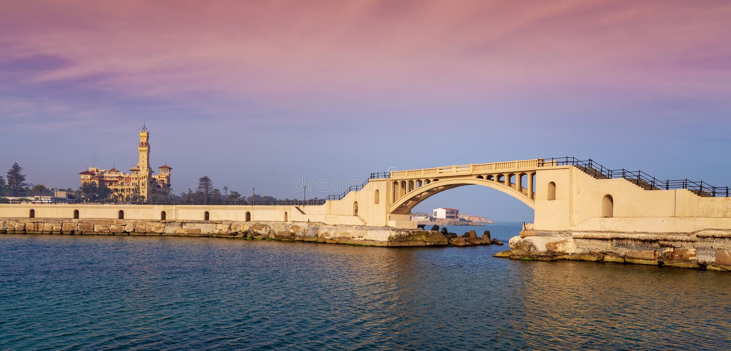 Мост в море на парке Montazah с королевским дворцом в далеком расстоянии с штилем на море на времени восхода солнца, Александрией стоковая фотография rf