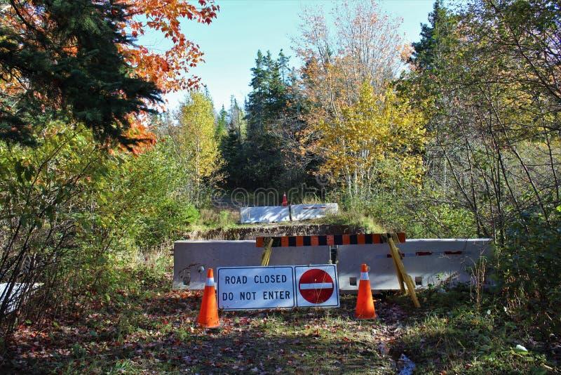Мост который был помыт вне с баррикадами цемента и оранжевыми пластичными конусами с a не вписывает знак вдоль сельской дороги стоковые фото