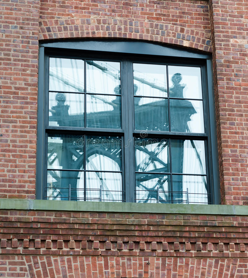 Мост Манхаттана отраженный в окне кирпичного здания стоковые фотографии rf