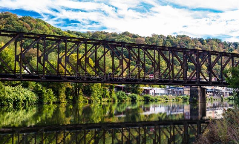 Мост металла железнодорожный над речным руслом в лесе на заднем плане деревьев в цветах осени стоковые изображения rf
