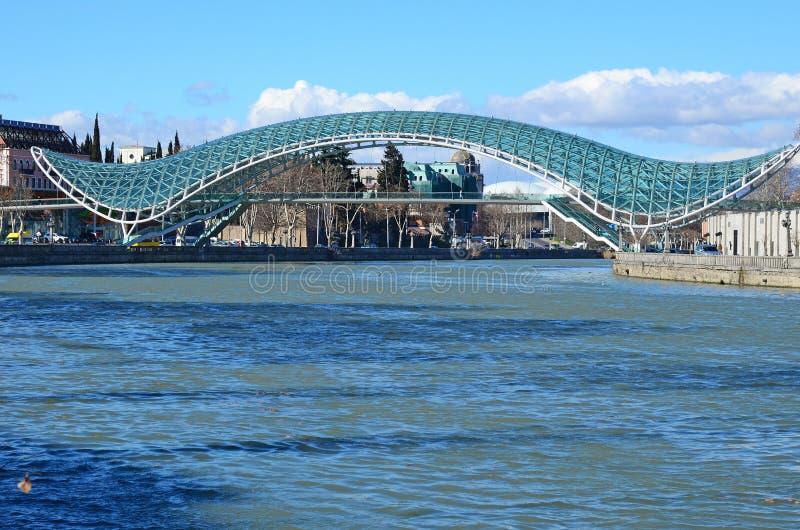 Мост мира - футуристический пешеходный мост над Рекой Kura tbilisi стоковые фотографии rf