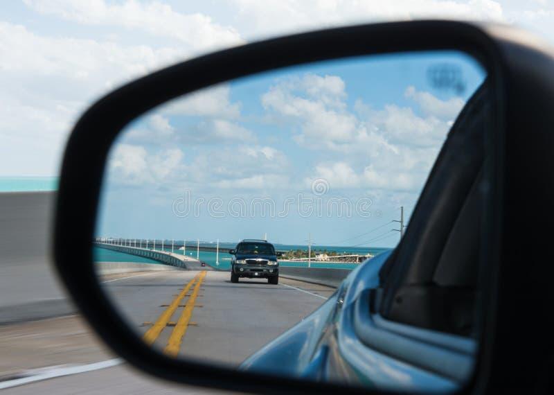 Мост 7 миль отраженный в зеркале автомобиля стоковая фотография