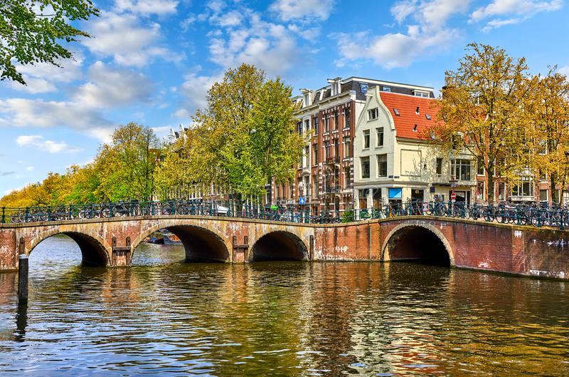 Мост над каналом в Амстердам Нидерланды расквартировывает ландшафт весны города ориентир ориентира Amstel реки старый европейский стоковые фото