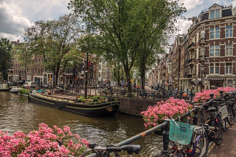 Мост над каналом с цветками, велосипедами, старыми зданиями и шлюпками в Амстердаме стоковые изображения rf