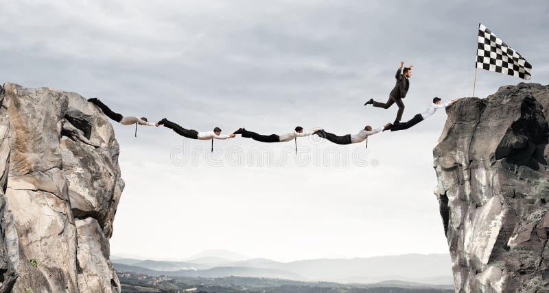 Мост поддержки бизнесменов, который нужно получить к флагу Концепция цели бизнеса достижения стоковое фото rf